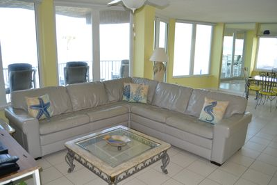 View of the living room overlooking the balcony, beach and ocean.