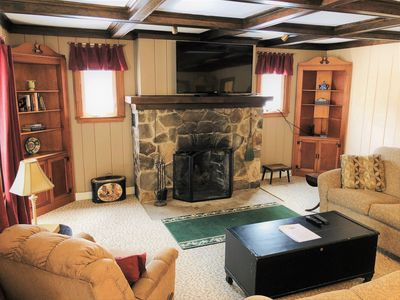 """Enjoy a cozy fire or your favorite shows on the 60"""" flatscreen TV."""