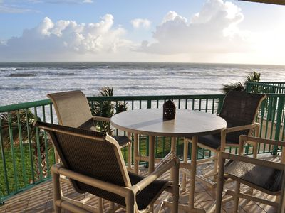 Balcony with amazing ocean front views with table and chairs.