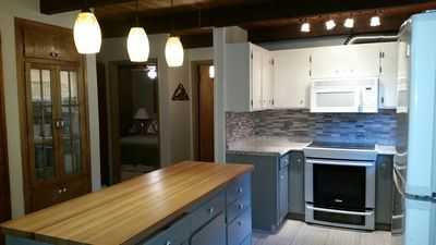 The large well lit kitchen island provides lots of space for everyone to gather.