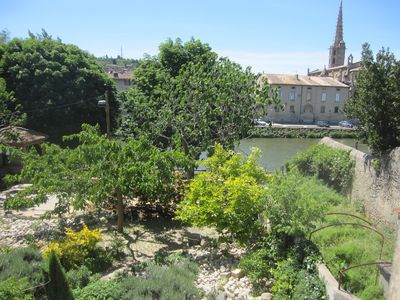 View of garden, river and church from balcony outside living room