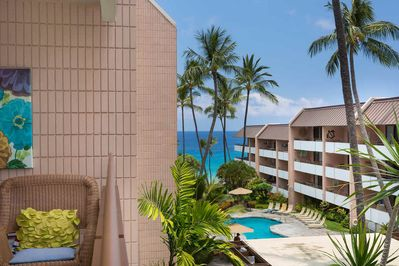 Covered lanai overlooking pool area and distant blue ocean