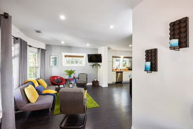 Open living room with comfortable seating for all, sleeper sofa, and TV loaded w
