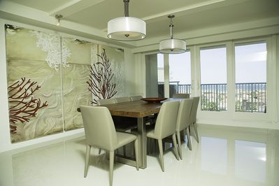 White Leather dinning chairs on the dining area for 8 guests.