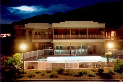 Swimming pool at night with conference centre  & office behind. Spa above.