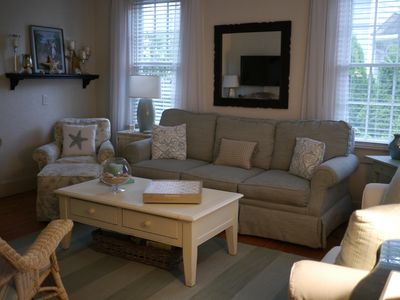 Comfortable living room with a sofa, love seat, large TV, and music