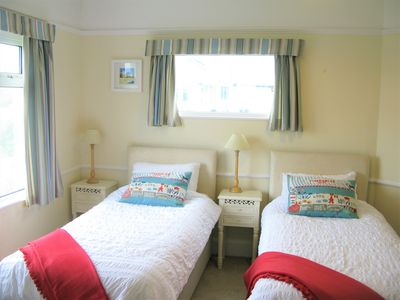 Double aspect twin room, with wardrobe, chest of drawers and sink.