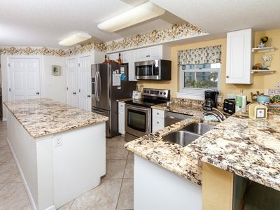 This full size kitchen has tons of counter space. At the left is - This full size kitchen has tons of counter space. At the left is part of a long island counter, and at the right the counter wraps around from the stove to the sink.