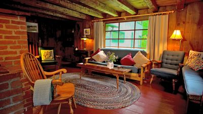 Another view of the living room with braided rugs and hand hewed beams