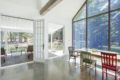 French doors open onto a covered porch and the creek, dam and waterfall beyond.