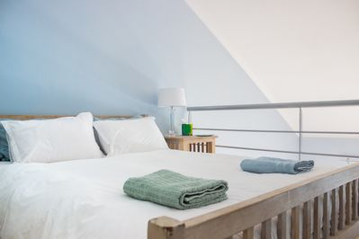 Bedroom in loft area with double bed, bedside table and lamp.