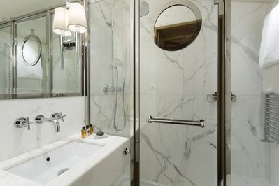 Two Carrara marble bathrooms with luxurious showers, plus a guest bathroom.