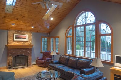 Living room with wood burning fire place, TV,  and ceiling fan.