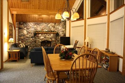 dining and living room with river rock wall and gas fireplace