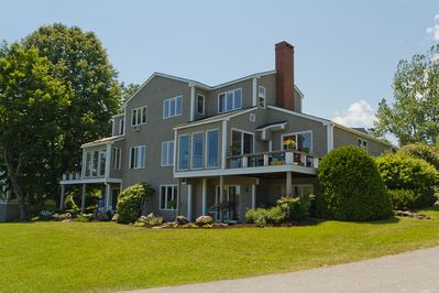Exterior of home facing Rockport Harbor. Large windows frame booming water views