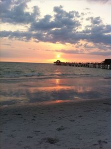Sunset at Naples Pier with pristine sandy beaches.