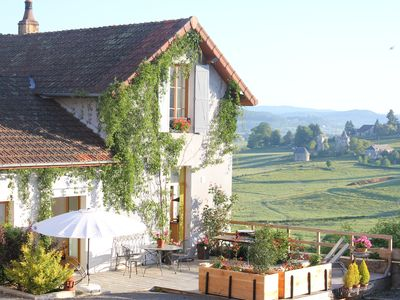 Photo for Stylish living in the village square with a large terrace overlooking the Morvan