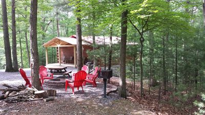 RED ROOF LOG CABIN WITH 8 ADIRONDACK CHAIRS TO ENJOY  THE FIRE PIT