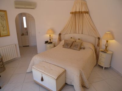 Master bedroom, which is circular, with king size bed and arch to dressing room