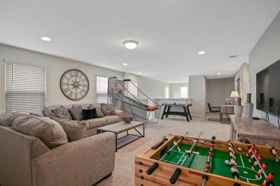 Entertainment room including foosball table, air hockey, and flat screen TV with cozy seating
