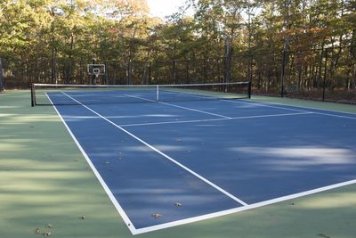 Expansive private tennis court with  basketball hoop