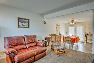 The living room offers comfortably seating arrangements and carpet flooring.