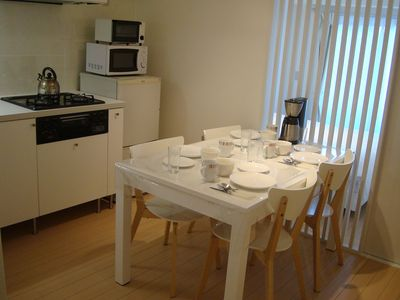 Dining table and chairs with fully equipped kitchen.