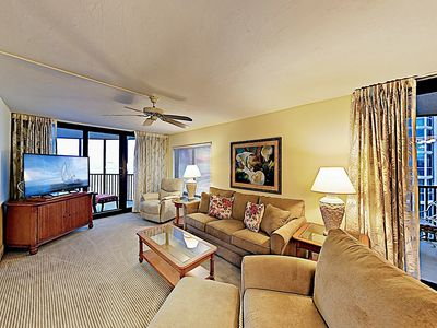 """Living Room - In the living room, a couch and armchairs surround a 47"""" flat-screen TV."""