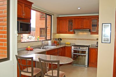Large, fully stocked kitchen with GE appliances, granite countertops and bar.