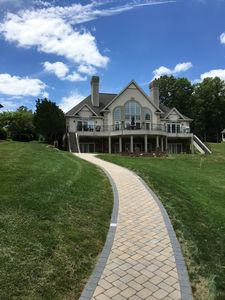 View from dock, showing walkway, fire pit, lower patio and upper veranda.
