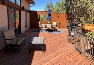 Fenced patio with table, glider, & 4 burner BBQ with two propane tanks.