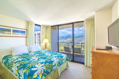 Bedroom with beautiful mountain and city views, queen size bed and TV