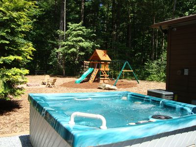 Private hot tub with fresh water on your arrival. Kids' play set in back ground.