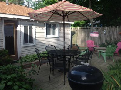 Privite patio with grill, umbrella, night time party lights and lots of flowers.