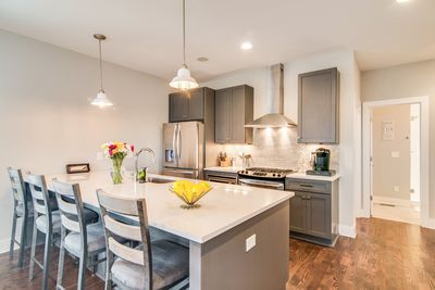 Kitchen - Channel your inner chef in the gourmet kitchen featuring white quartz counters and trendy grey cabinets