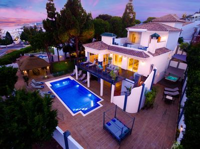 aerial night shot of pool and villa with la cala de Mijas  in the back ground.