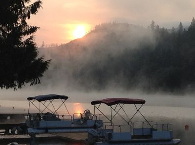 Watch the sun rise over the hills as the early morning mist dances on the lake