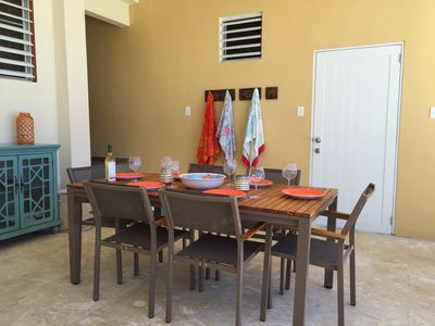 Dining outside in the shade with a ceiling fan above  and tableware