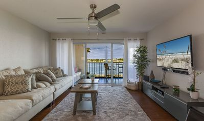 The living room features a leather sectional sofa, large flat screen TV and sliders to the riverfront patio.