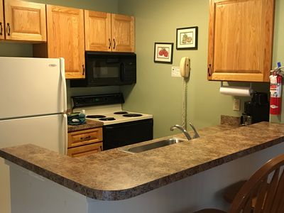 Kitchen complete with stove, microwave, toaster, coffee machine, and dinnerware