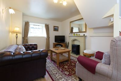 Log effect stove adds atmosphere to this centrally heated warm living room