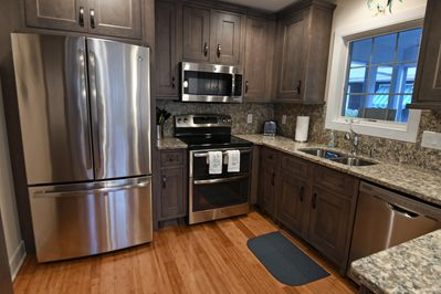 Kitchen with S/S appliances, granite counter, room for guest items.