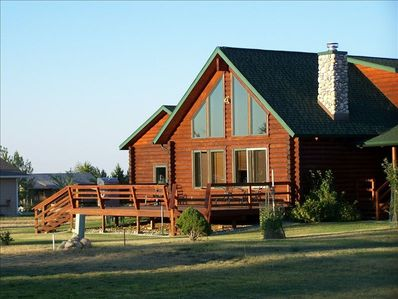 West-facing view of log cabin, large deck with barbeque grill, bench seating ++