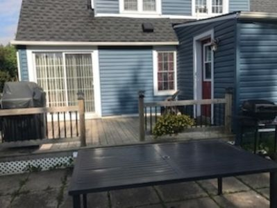 back deck with barbecue, table and seating for six overlooking spacious backyard