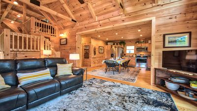 Open kitchen/ living room with vaulted pine ceiling and windows everywhere