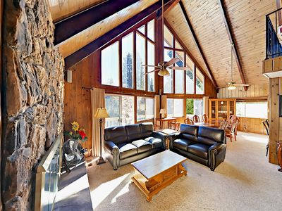 Great Room - Great Room with sofa, love seat, stone fireplace, vaulted ceilings and a dramatic wall of windows.