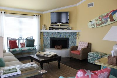 Coastal decorations adorn the living room that is open to the kitchen and dining room