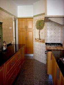 The Portuguese tiled kitchen with gas stove, oven, fridge, kettle and microwave.