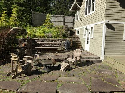 Patio with sitting area around fire pit, picnic table, and charcoal grill
