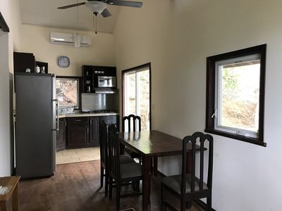View of dining area & table. The full sized kitchen, fridge, oven & AC  seen.